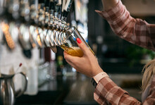 Brewery: Female Bartender Pouring A Beer