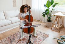 Hispanic Cello Student Rehearsing In Living Room