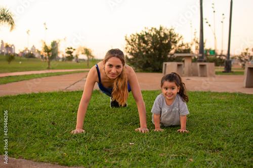 Foto madre e hija haciendo flexiones de brazos en un parque al aire libre