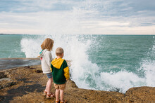 Two Children Standing On A Pier With Breaking Waves