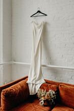 White Wedding Dress Hanging On White Brick Wall Of Loft Onto Burnt Orange Velvet Couch
