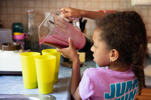Young Girl Pouring Blended Smoothies Into Cups