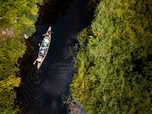 People Using Canoe To Travel Narrow Waterway Between Green Shore