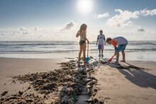 Three Children Dig A Trench At Beach