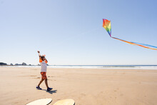 Young Black Boy Flies Rainbow Kite At The Beach