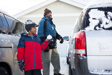 Father And Son Clean Snow Off Vehicle