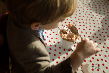Child Spoons Marshmallows From An Overflowing Hot Chocolate Cup.