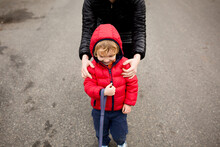 Mother Holds Shoulders Of Grinning Boy With Dog Leash