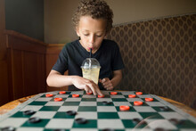 Boy Playing Checkers While Sipping From Cup
