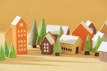 Miniature Houses With Fir Trees On Yellow Background