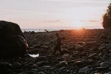 Man Walks Along A Rocky Beach.