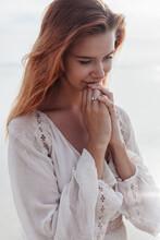 Young Woman Praying On Beach