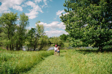 Two Girls Stand By A Pond Outdoors In Summer.