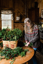 Florist Making Holiday Wreath  With Holly