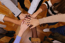 Company Of Diverse Friends Stacking Hands Together