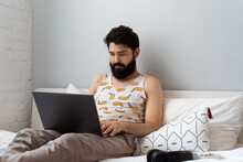 Bearded Guy Resting On Bed With Laptop