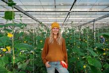 Cheerful Female Farmer Amidst Cucumber Plants