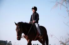 Asian Little Girl Playing On Horseback In The Wild Horse Farm