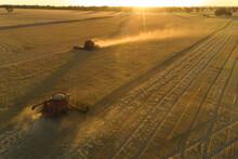 Headers Harvest Crop At Sunset In Australia