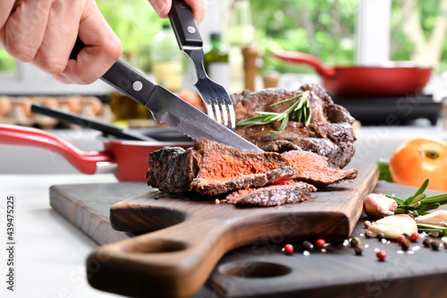 Fotografie, Obraz Hand slicing grilled beef steaks with spices on wooden cutting board in the kitc