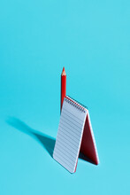 Red Pencil And Spiral Notepad
