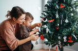 Mom and baby adding decorations to Christmas tree