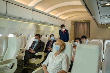 Air hostess wearing protective mask to Protect Against Covid-19 take care and check the orderliness of the plane passengers before departure,Air travel during the coronavirus pandemic.