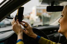 Close-up Of Senior Woman Placing Her Phone On The Gps Holder At Car