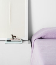 Minimalistic Bedside Table With Books, A Dog Figurine And A Framed Picture Next To  Bed