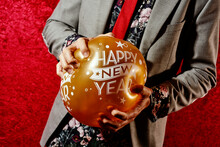 Smashing A Balloon That Reads Happy New Year