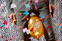 Man Squeezing A Balloon That Reads Happy New Year