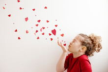 Young Girl Blowing Hearts Towards The Sky