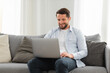 Happy caucasian man uses laptop computer for video call while sitting on sofa at home, smiling caucasian man chatting with friends or family via video conference on social networks