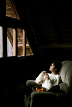 Cute, Curly-haired Girl Sitting In Armchair And Dreaming About Better Future.
