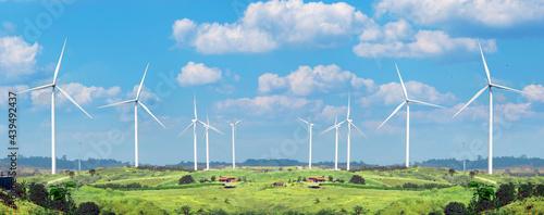 Fotografiet Wind Turbine Alternative on a green meadow and blue sky banner