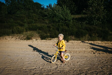 Boy With Yellow Raincoat And Bike On The Beach