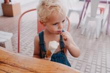 Little Blond Boy Eating Ice Cream Outdoors