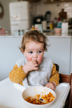 Baby Girl With Polkadot Dress Eating Pasta In A High Chair