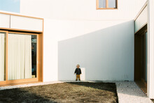 Boy Standing Outside A White Modern Home