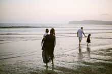 Family Wading In Ocean At Sunset