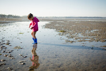 Girl In Boots Wading In Shallow Water