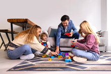 Mother, Father And Kids Playing With Toys At Home