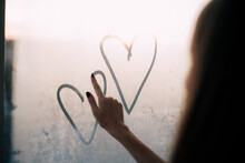 Young Woman Drawing Hearts On The Window