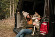 Young Woman In Camper Van With Wolf Dogs In The Mountain