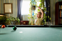 Boy At Pool Table Raises Fist In Victory