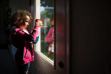 Girl Sprays Dirty Window