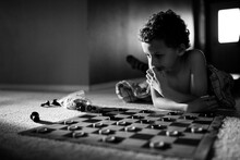 Boy Plays Checkers On Floor