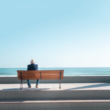 Senior Man Sitting On A Bench Looking Out To Sea