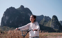 Natural Lively Asian Little Girl Riding A Bicycle In The Cornfield Outdoors In Autumn