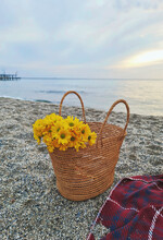 Yellow Flowers In A Basket By The Sea